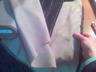 A roll of canvas and the skeleton baste of an overcoat, canvas visible, ready for the customer's first fitting