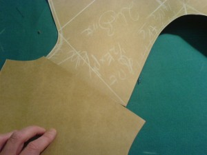 The forepart and the back of a freehand cutting pattern, meeting at the shoulder seam. Note how the back part - at the bottom of the photo - is much longer than the forepart